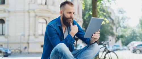 ein Mann schaut auf sein Tablet